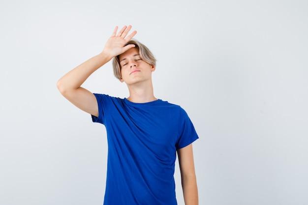 Bel ragazzo adolescente in maglietta blu che tiene la mano sulla testa, chiude gli occhi e sembra stanco, vista frontale.