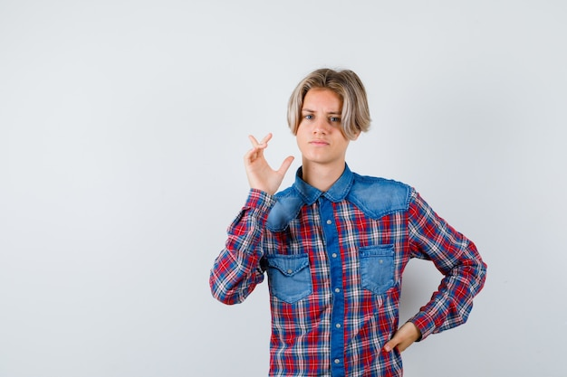 Bel ragazzo adolescente in camicia a quadri che punta all'angolo in alto a sinistra e sembra premuroso, vista frontale.