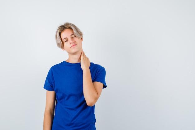 파란색 티셔츠를 입은 잘생긴 10대 소년은 목이 아프고 피곤해 보입니다.