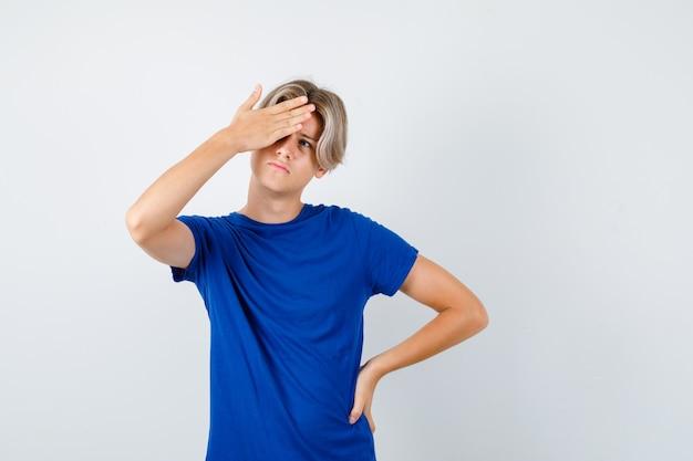 파란색 티셔츠를 입은 잘생긴 10대 소년은 손을 잡고 위를 쳐다보고 잠겨있는 앞모습을 보고 있습니다.