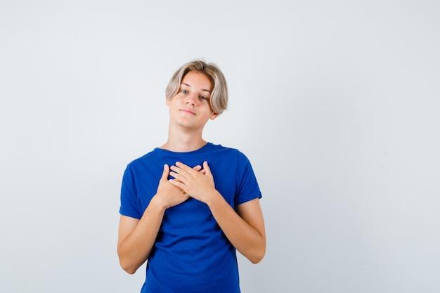 파란색 티셔츠를 입은 잘생긴 10대 소년은 가슴에 손을 얹고 감사하게 바라보고 있습니다.