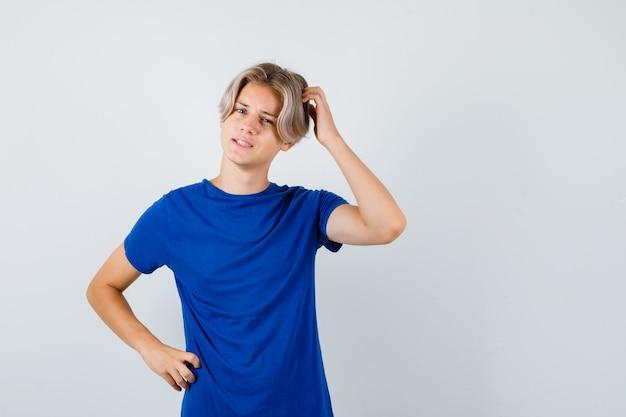 파란색 티셔츠를 입은 잘생긴 10대 소년은 머리를 긁적이며 건망증을 찾고 있습니다.