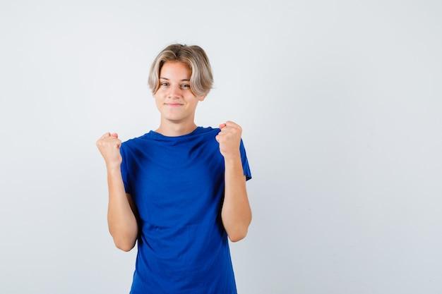 Красивый мальчик-подросток в голубой футболке показывает жест победителя и рад, вид спереди.