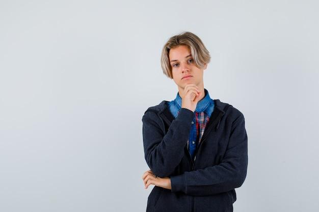 셔츠를 입은 잘생긴 10대 소년, 후드티를 손에 들고 우울한 앞모습을 보고 있습니다.