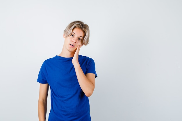青いtシャツで手に頬を傾けて物思いにふける、正面図を探しているハンサムな10代の少年。