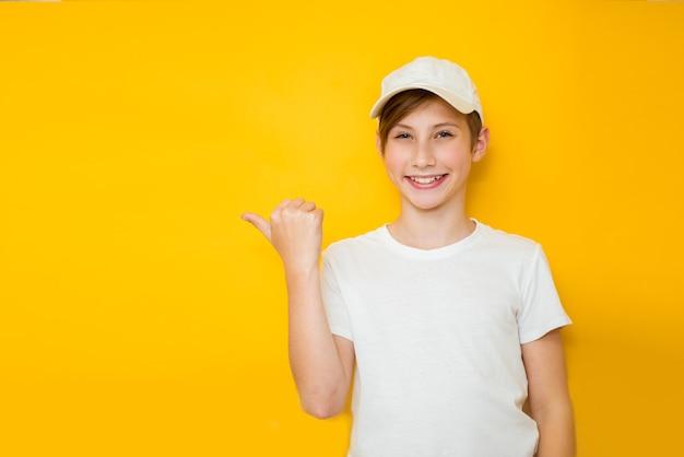 Красивый мальчик-подросток на желтом фоне в белой футболке и кепке улыбается счастливым лицом, указывая в сторону с большим пальцем вверх