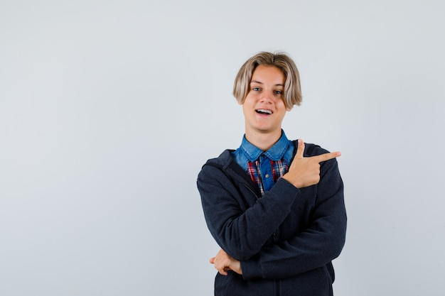 Handsome teen boy pointing right in shirt, hoodie and looking glad , front view.