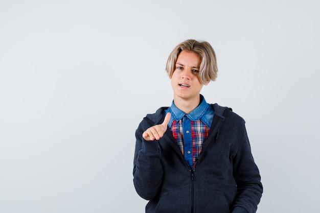 Bel ragazzo adolescente in camicia, felpa con cappuccio che mostra il gesto di arresto e sembra fresco, vista frontale.