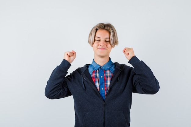 Красивый мальчик-подросток показывает жест победителя, держа глаза закрытыми в рубашке, толстовке с капюшоном и выглядит взволнованным, вид спереди.