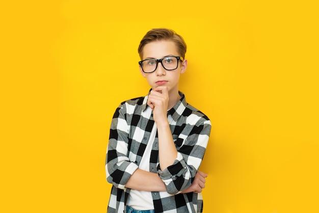 黄色の背景にジェスチャーを考えるハンサムな10代の少年