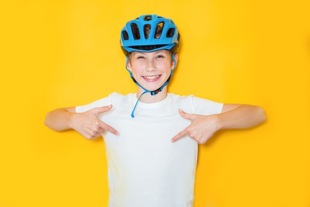 Handsome teen boy wearing cyclist safety helmet over isolated yellow background. winner concept