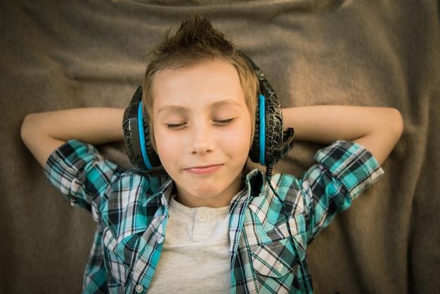 ハンサムなティーンが横たわって、ヘッドフォンで音楽を聴きます