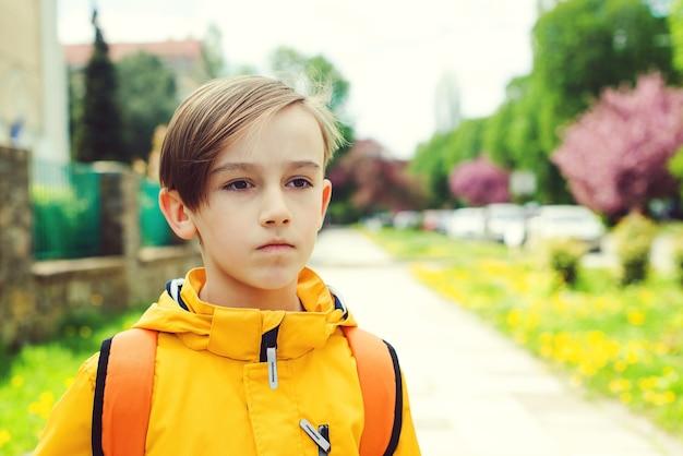 学校に行くハンサムな10代の学生。バックパックを持つかわいい男の子。新学期の始まり。深刻な男子生徒の屋外の肖像画。教育、学校、ライフスタイルのコンセプト。