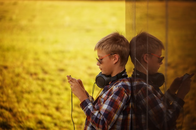 Handsome teenage boy listening to music and using phone