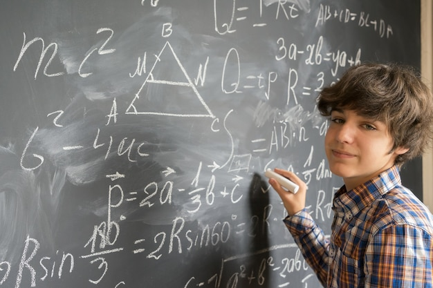 黒板にチョークで複雑な数式を書くハンサムな10代の少年