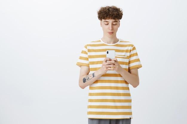 Bel ragazzo adolescente in posa contro il muro bianco