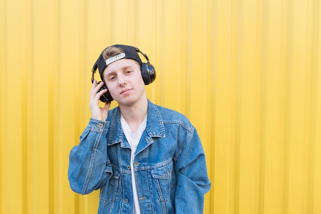Handsome teenage man stands with headphones on a lively wall