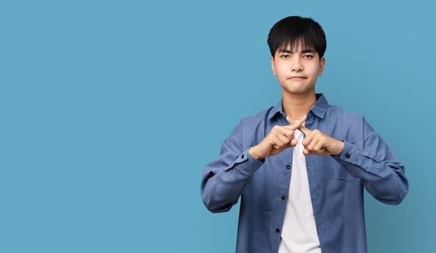 ハンサムなティーンエイジャーのアジアの少年の拒否表現は、否定的な兆候をしている指を交差させ、煙や麻薬や麻薬を止めるために怒った顔をしています。
