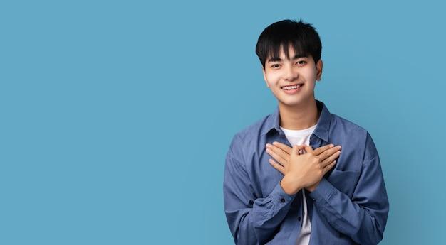 おめでとうございます、笑顔と心に手を押して、青い背景の上に立って、ありがとうと印象的なハンサムなティーンエイジャーのアジアの少年。