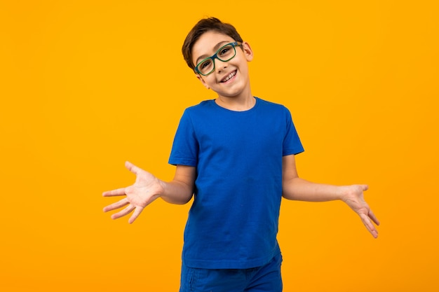 Handsome teenager boy in a blue t-shirt with glasses holds out his hands in different directions on yellow with copy space