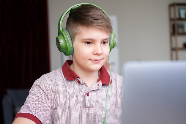 Handsome teenager boy in headphones studying online, playing in video games using laptop sitting on kitchen.