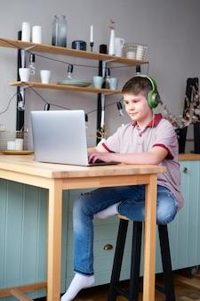 Красивый мальчик-подросток в наушниках учится онлайн, играя в видеоигры, используя ноутбук, сидя на кухне.