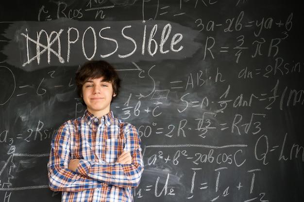 不可能な言葉の下に立っているハンサムなティーンエイジャーの少年は、背景の数式で黒板に可能になりました