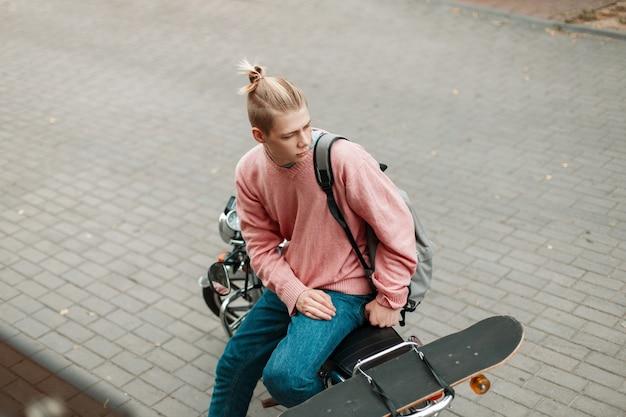 Красивый подросток мужчина в розовом свитере с рюкзаком и скейтбордом сидит на мотоцикле