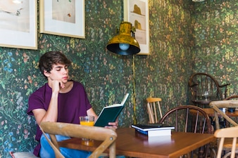 Handsome teenager reading in cafe