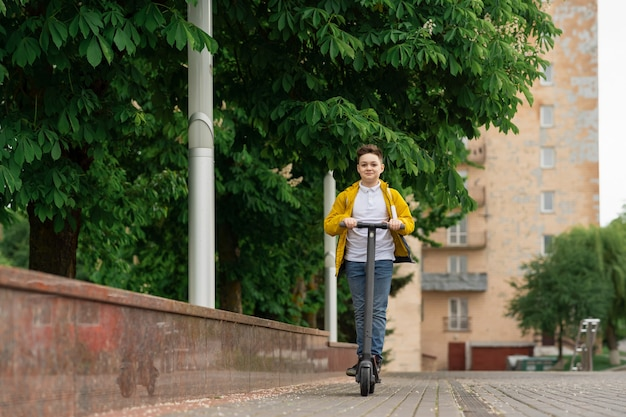 ハンサムなティーンエイジャーが街の通りを電動スクーターに乗る
