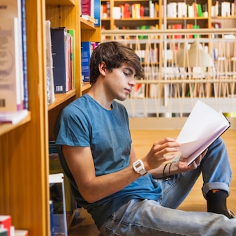 Handsome teenager turning pages of book