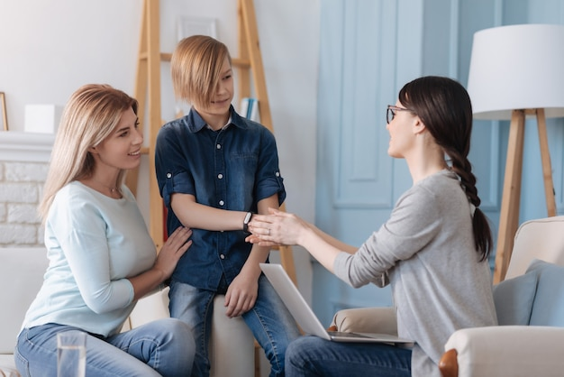 Handsome teenager wearing jeans costume having stylish haircut giving his hand to his psychologist