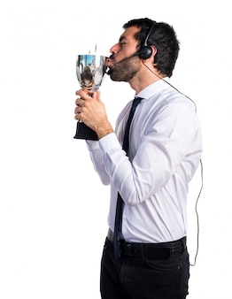 Handsome telemarketer man holding a trophy