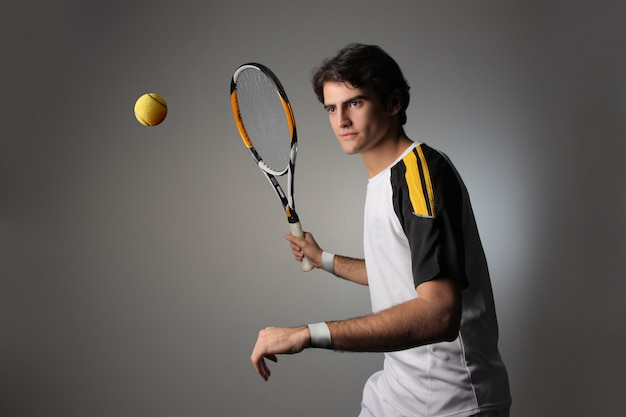 Handsome tennis player in action