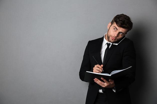 ハンサムな思考のビジネスマンが携帯電話で話しながらメモを取って、よそ見