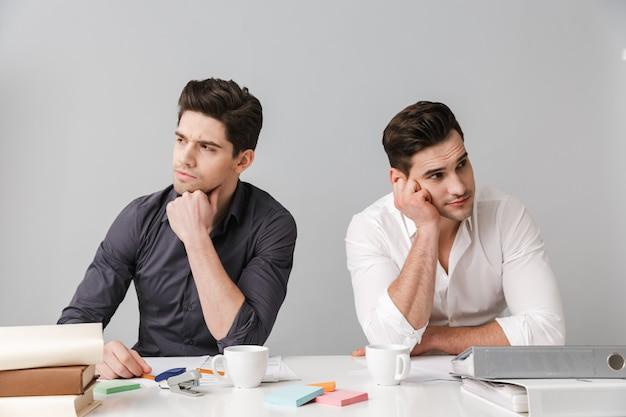 ハンサムな思慮深い2人の若いビジネスマンを集中