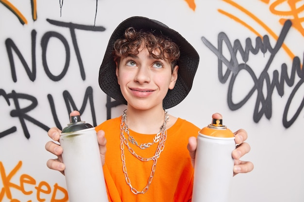 Handsome thoughtful curly haired teenager concentrated above holds two paint cans creats graffiti wall wears hat orange t shirt metal chains around neck uses aerosol spray being pat of street gang