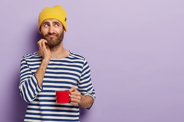 Handsome thoughtful young man with bristle, holds mug of coffee, has pensive look, break after work, wears striped jumper, yellow headgear