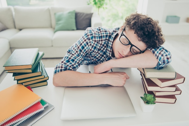 Красивый усталый молодой парень дома ботаник в очках спит лицом на книгах