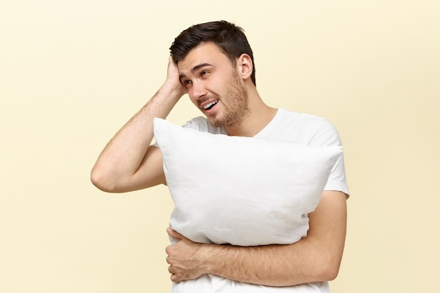 Handsome tired young man holding white pillow