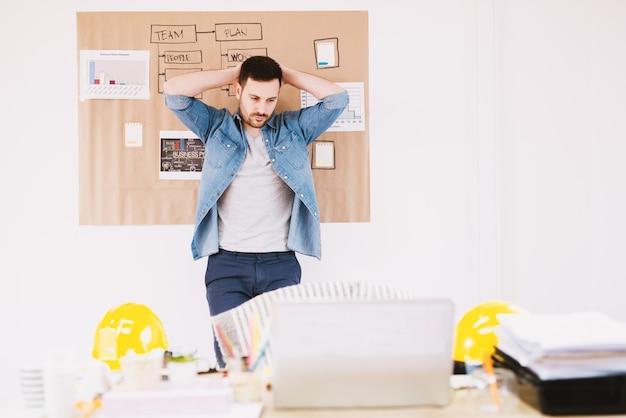 ハンサムな疲れた若い現代ビジネスの男性が椅子から立ち上がって頭の後ろに手を繋いでいると仕事を休憩します。