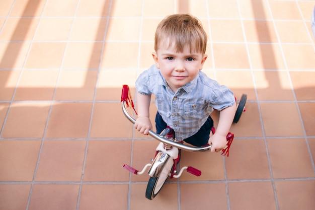 自宅で自転車に乗ることが困難なハンサムな幼児。