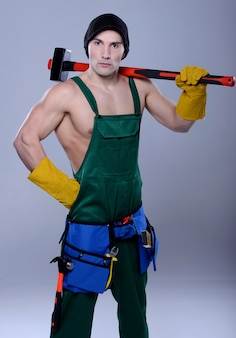 Handsome topless construction worker with sledge hammer.
