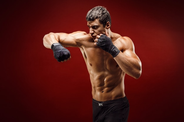 Handsome topless sportsman practicing punches