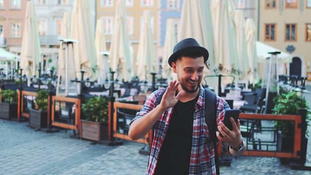 Handsome tourist making video call on smartphone and showing his place of visit