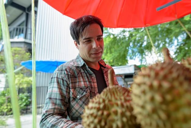 ストリートショップでドリアンの果物を買うハンサムな観光客の男