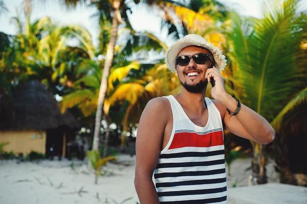 Красивый туристический мужчина разговаривает по смартфону на фоне пальм