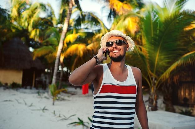 Красивый туристический человек разговаривает по смартфону на фоне пальм