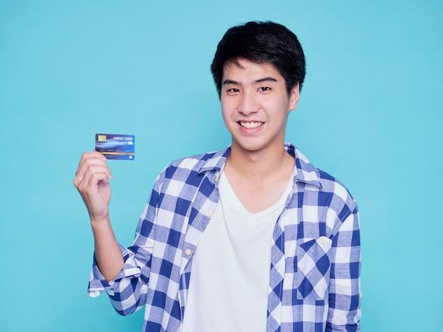 Красивый туристический человек с кредитной картой на голубой стене. концепция летнего путешествия