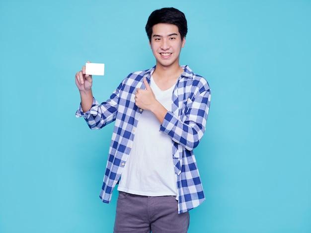 水色の壁にクレジットカードを持つハンサムな観光客の男。夏の旅行のコンセプト